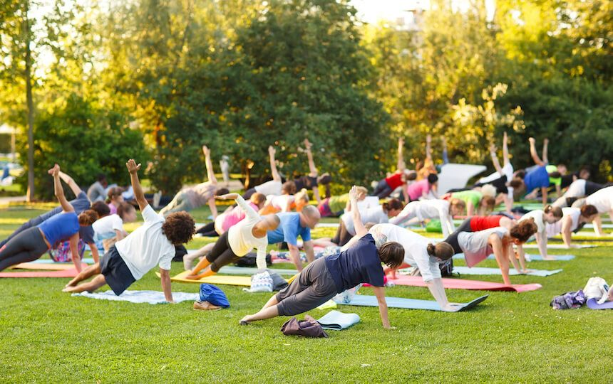 A crowd of people are using yoga mats in a park setting, performing a yoga stretch.