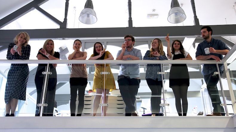 The Social Change UK team stand on the mezzanine balcony in the office, talking and smiling.