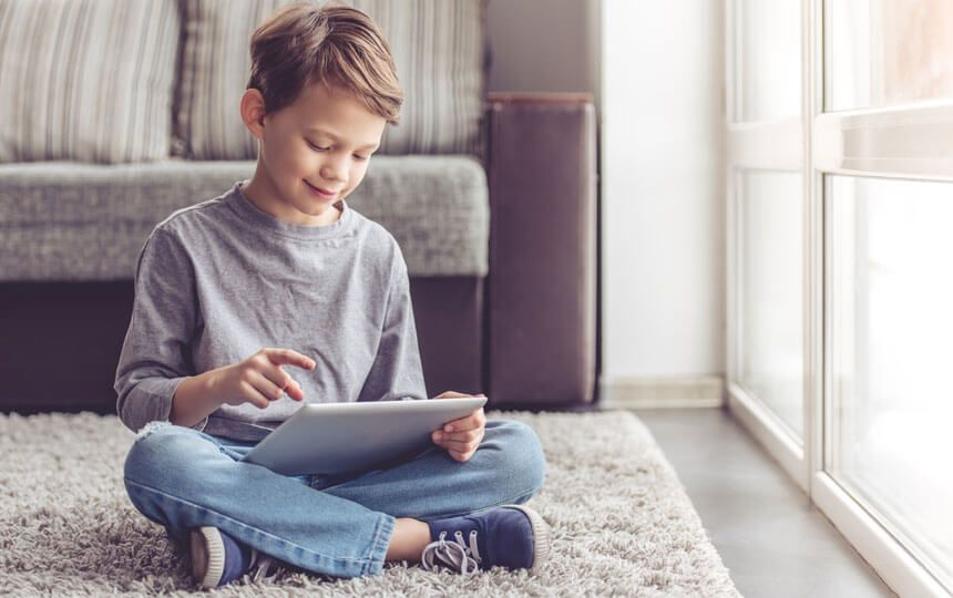 A young boy is sat on a rug at home smiling down at an iPad in his hands.