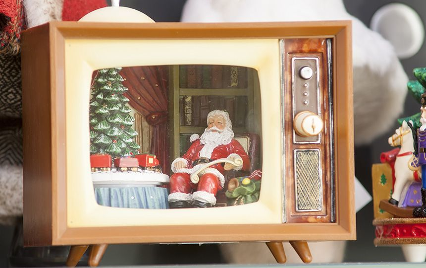 A Christmas ornament of a television showing Santa Clause sat beside a decorated tree.
